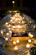 An outdoor table with plenty of votive candles looks stunning