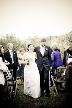 Walking back down the 'aisle', with guests throwing rose petals on us