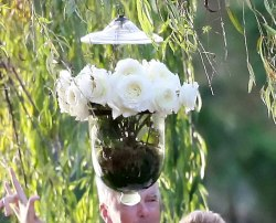 Roses in glass jars were hung at the ceremony site of Molly Sims and Scott Stuber's wedding
