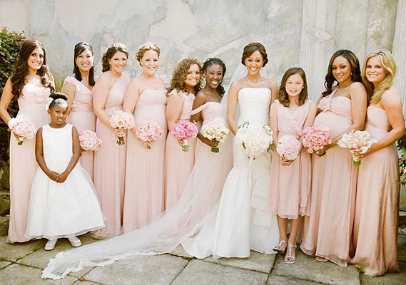 Tamera Mowry's bridesmaids dressed in light pink dresses of the same shade, but carried pink roses of varying shades