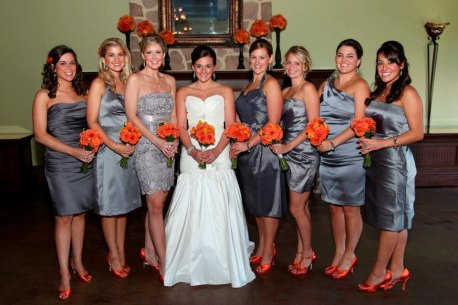 Bridesmaids in grey with orange bouquets