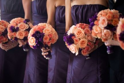 Bridesmaids in dark purple with peach bouquets