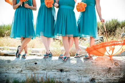 Bridesmaids in teal dresses with orange bouquets