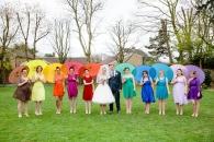 Bridesmaids in rainbow dresses with matching parasols {via boho-weddings.com}