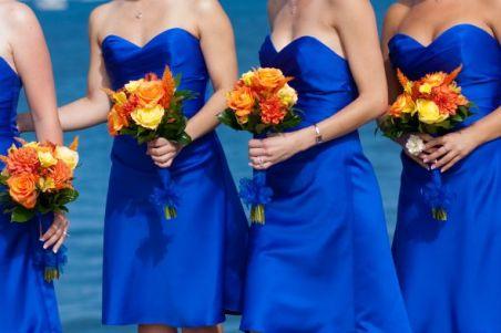 Bridesmaids in cobalt blue with orange bouquets