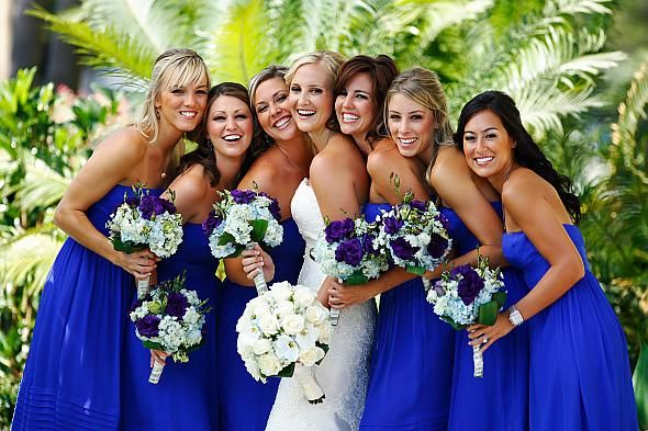 Bridesmaids in royal blue dresses with purple and white bouquets ...