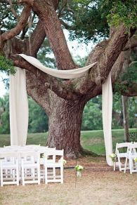 Fabric draped over a tree to frame the ceremony area {via brit.co}