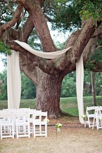 Fabric draped over a tree to frame the ceremony area {via brit.co}