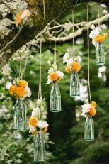 Hanging bottles with flowers look beautiful {via stylemepretty.com}